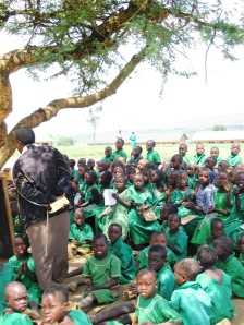 Rwimyaga Primary School, children under trees, teacher 2